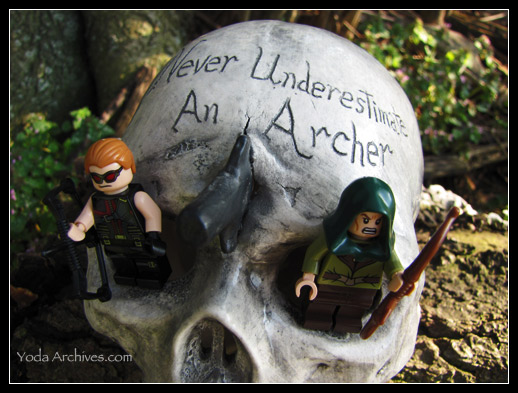 Lego Hawkeye and lego Mirkwood el minfigure stand in the eye sockets of a ceramic skull. The skull has an arrow head sticking in it. etched in the skull are the words,