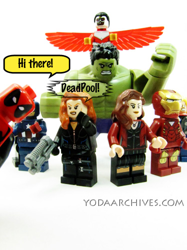 Lego avengers in a semi circle getting their picture taken when deadpool photobombs them