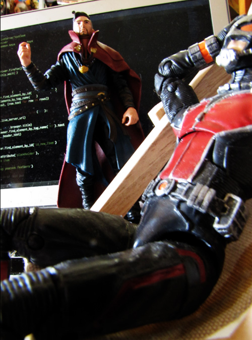 Doctor strange yelling at antman for goofing off. ant-man and dr strange action figures are in an office in front of a full size computer. ant-man is in a lounge chair being lazy.