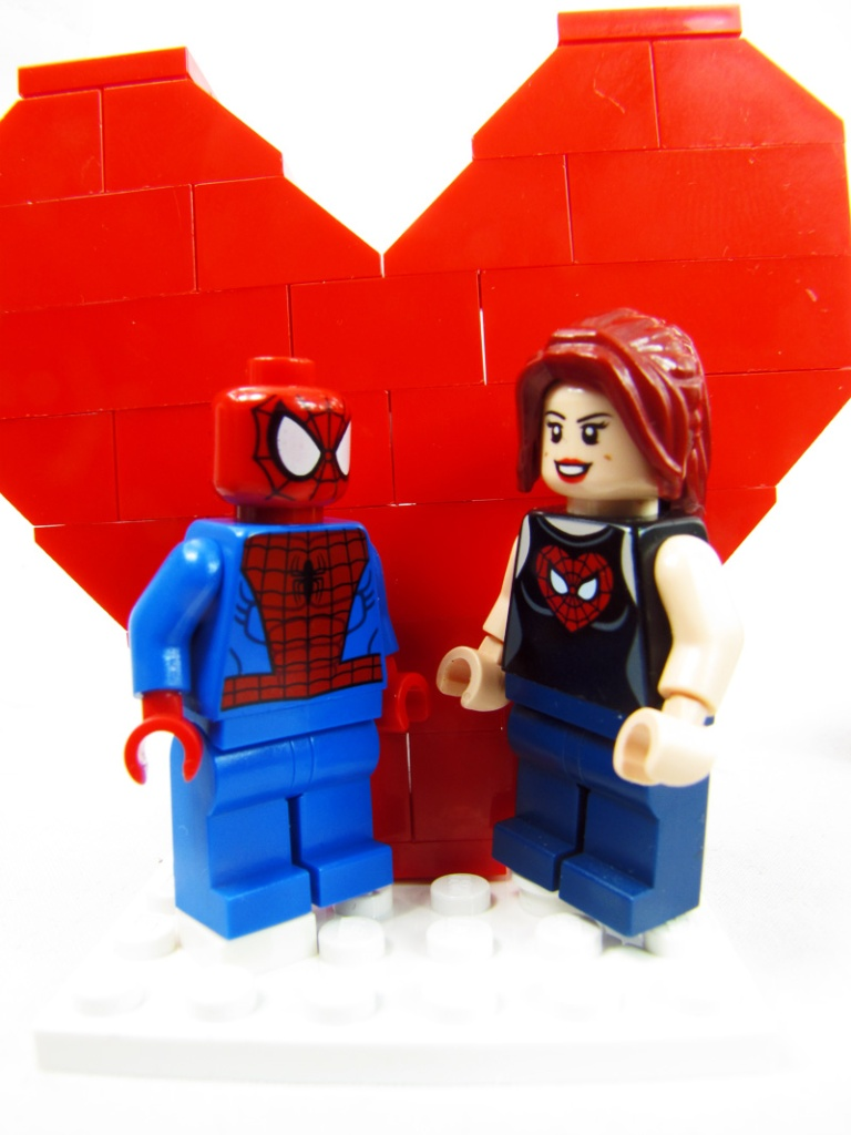 LEGO Spider-man and Mary Jane stand infront of a Heart made of LEGO Bricks.