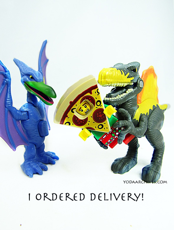 "Two toy dinosaurs are facing each other. The T-rex is holding a LEGO man wearing a costume pizza slice. The t-rex says ""I ordered delivery!"""