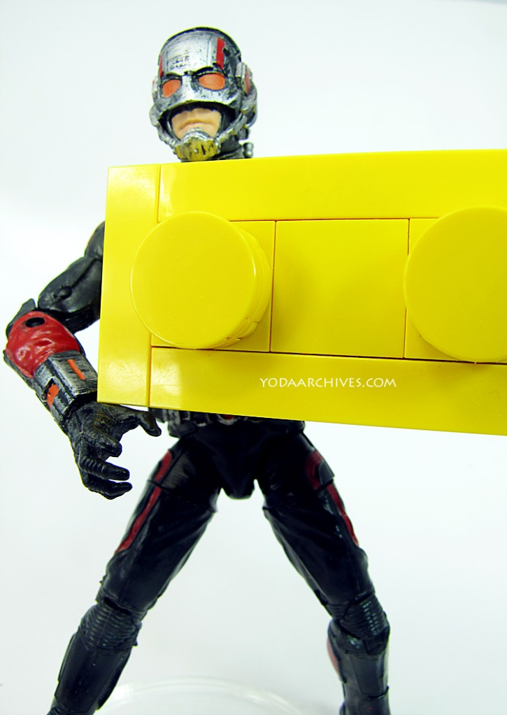 ant man holding a LEGO brick model. It.'t a large brick made of many LEGO pieces so it it half the size of the antman action figure.