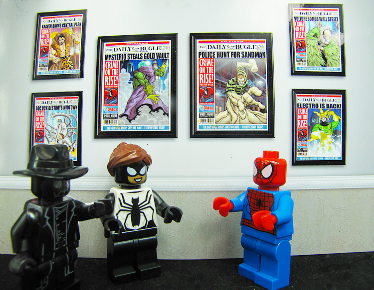 LEGO Spider-man and Spider-girl in a hallway. On the wall are framed editions of the daily bugle. text reads take your daughter to work day.