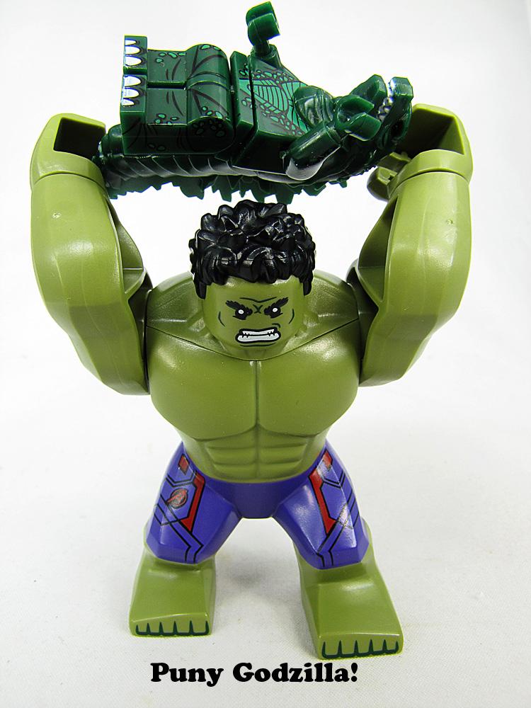 Giant size LEGO Hulk holding a smaller Godzilla minifig in  arms overhead. Like he's about to smash  godzilla to the ground. Hulk says Puny Godzilla.