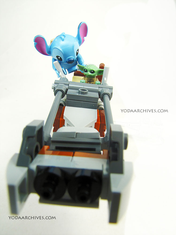 Stitch trying to drive a speeder bike. He's in the air holding on the the handle. Grogu is in the seat.