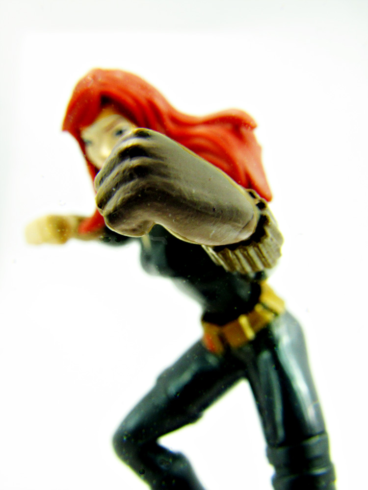 Black widow action figure. Her fist is in focus in the foreground. The rest of her is blurry. It looks like she is punching the viewer.